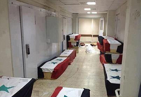 Syrian flags drape the coffins of some of those who died in the Aleppo University attack.